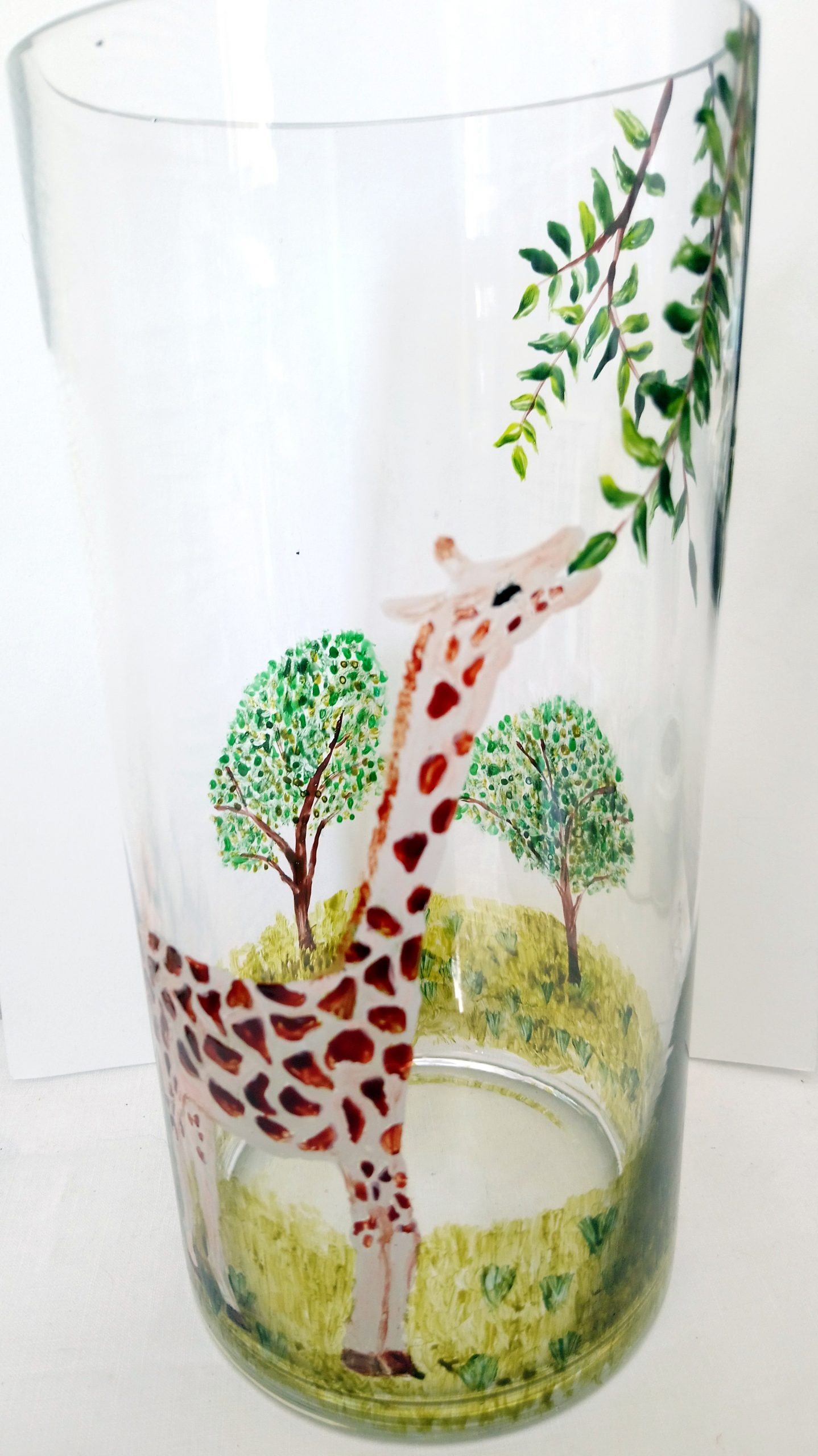 A Giraffe vase gift hand painted with a giraffe reaching up to leaves on a tree