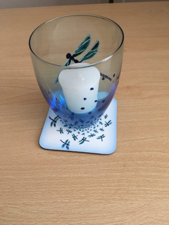 Abstract dragonfly coaster shown with a candle holder