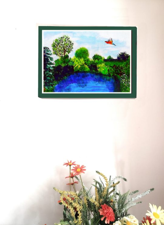 A4 wall art print with an English country garden scene of trees and plants around a pond with a kingfisher flying above.