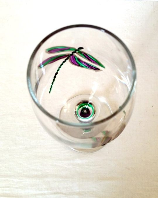 Hand painted wine glass showing the inside view of the dragonfly art