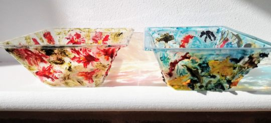Two recycled plastic dishes with abstract paintings