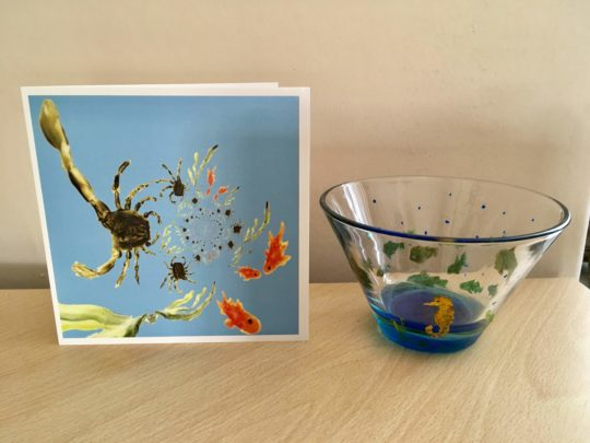 A card with an abstract rock pool with crabs and fish. Photographed with a bowl hand painted with fish