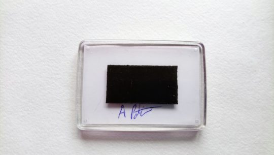 Back of a fridge magnet showing signature