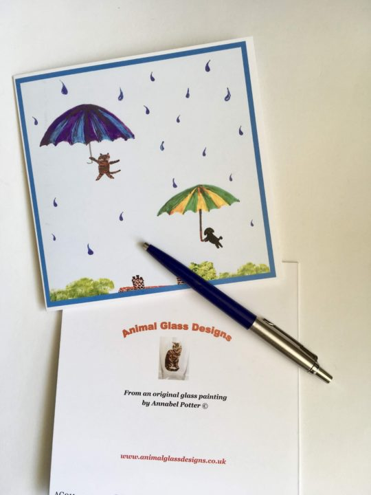Greeting card with raining cat and dog with umbrellas