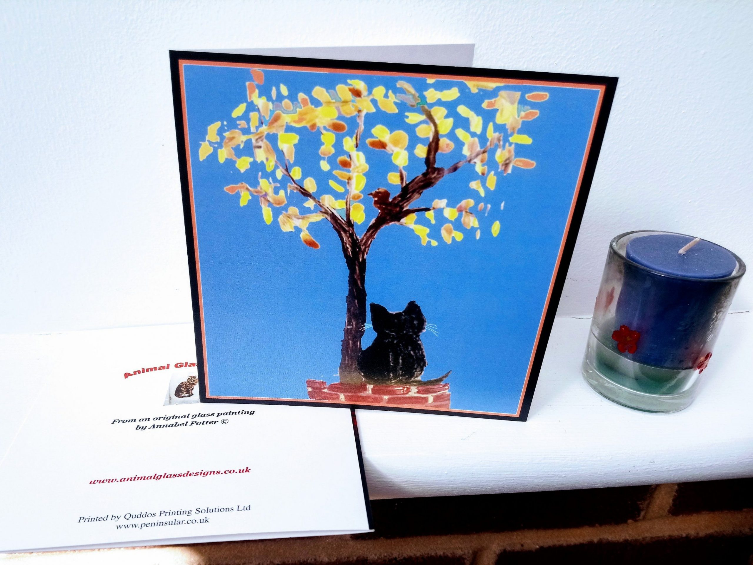 Greeting card with a cat sitting on a wall under a tree with Autumn leaves