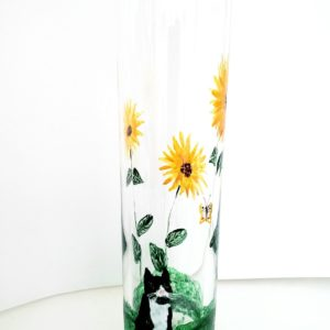 A bud vase with sunflowers and a black and white cat watching a butterfly. Hand painted with glass paints