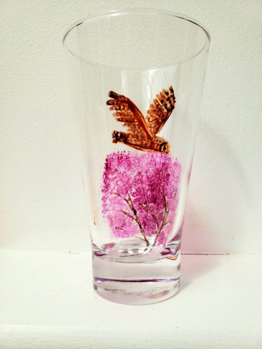 Glass painting with a brown owl flying and a blossom tree