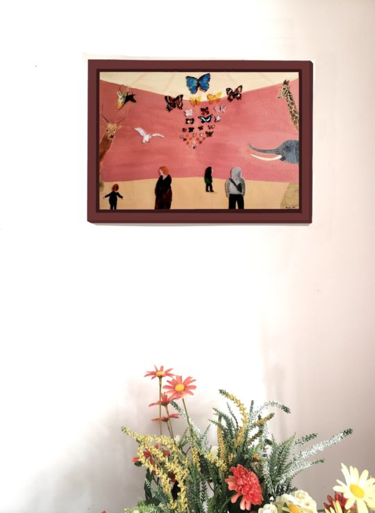 Wall art of animals at a museum and people in the foreground