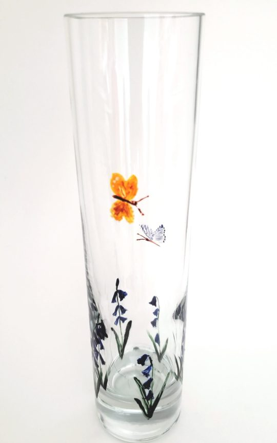 Hand painted glass vase with bluebells around the base and a yellow and blue butterfly flying above