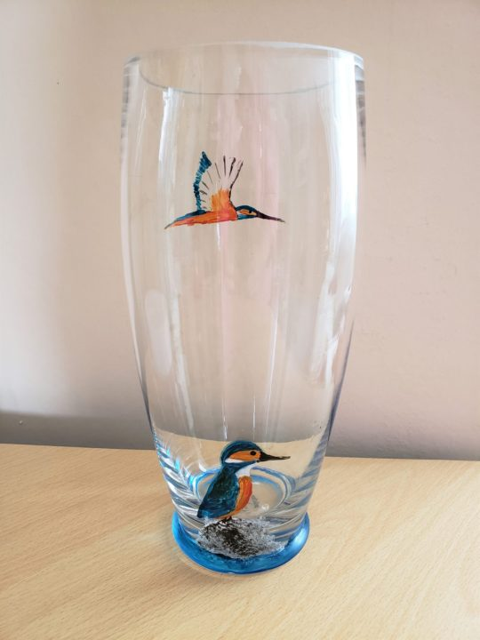 Glass vase with two kingfishers, one flying and another kingfisher perched