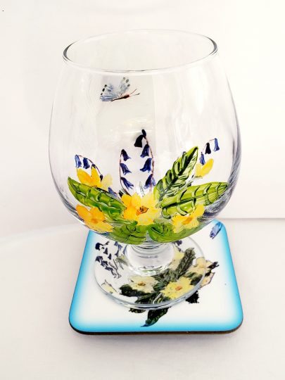 Hand painted wine glass and coaster with primroses, bluebells and a butterfly